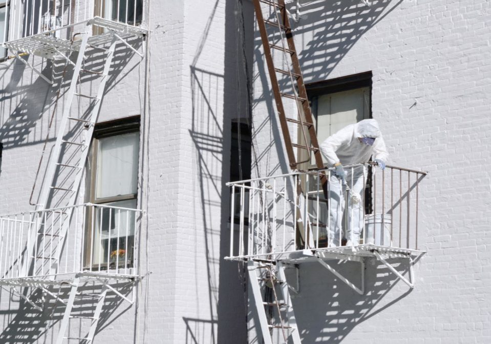 man paints the metal stairs